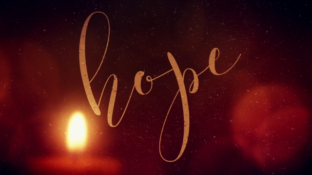 "A candlelit red background with the word ""Hope"" written in cursive"