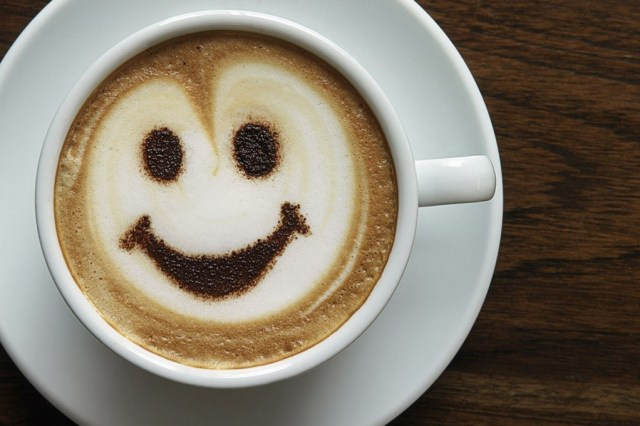 A photograph of a cup of coffee with a smiling face formed with the foam on top