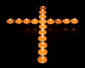 Photograph of a cross made from candles
