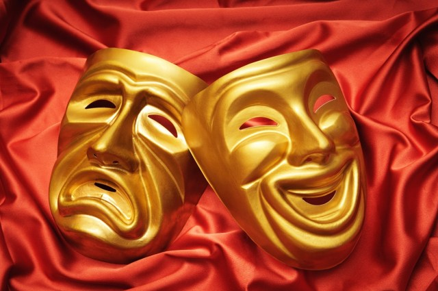 A photograph of a happy and a sad mask representing the theatre