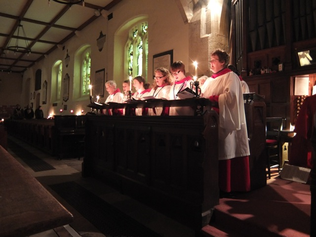 An image of a robed choir singing by candlelight in the church.