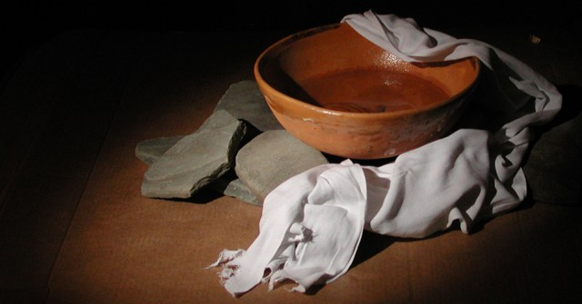 An image showing a bowl of water, cloths, and some stones, representing the footwashing of Maundy Thursday