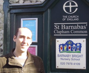A photograph of Rev'd Gerard Rundell standing outside St Barnabas', Clapham, where he was parish assistant
