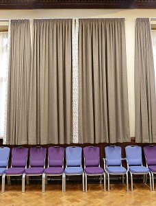 A photograph of curtains and purple chairs in St Michael's Parish Hall