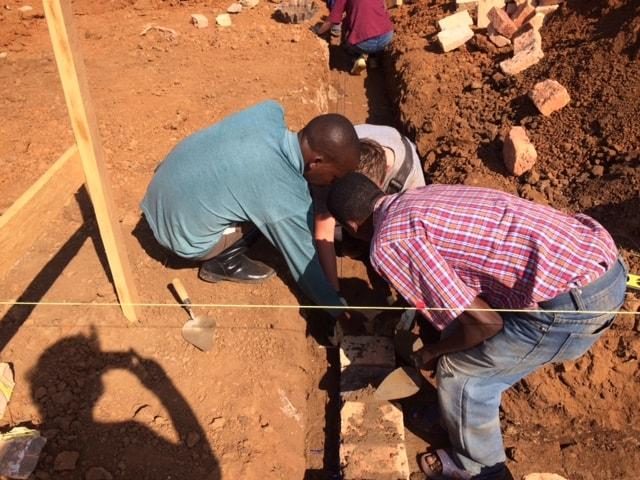 Men laying foundation bricks