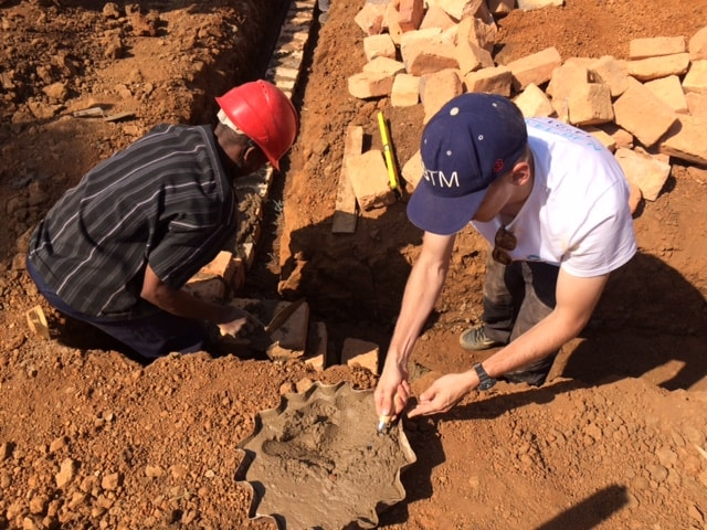 Slovanian team laying foundation bricks