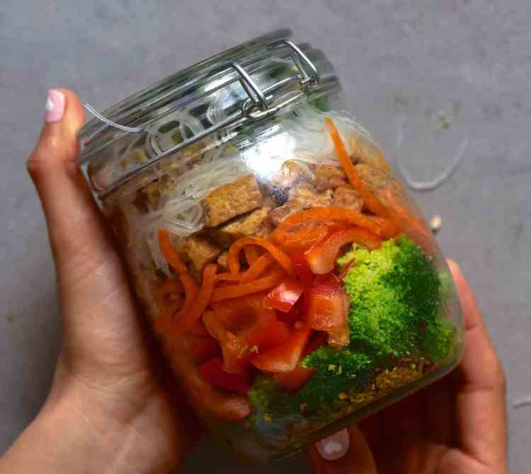 Thai inspired salad in a jar with noodles, broccoli , carrot, peppers, spinach, tofu, Thai salad dressing and peanuts