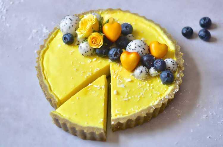 vegan pistachio & lemon tart topped with dragonfruit, roses, blueberries