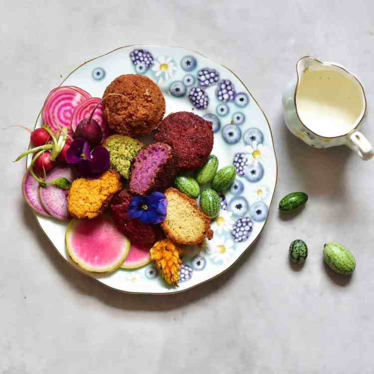Rainbow falafel with veggies, yogurt tahini dip and edible flowers as part of a mezze platter