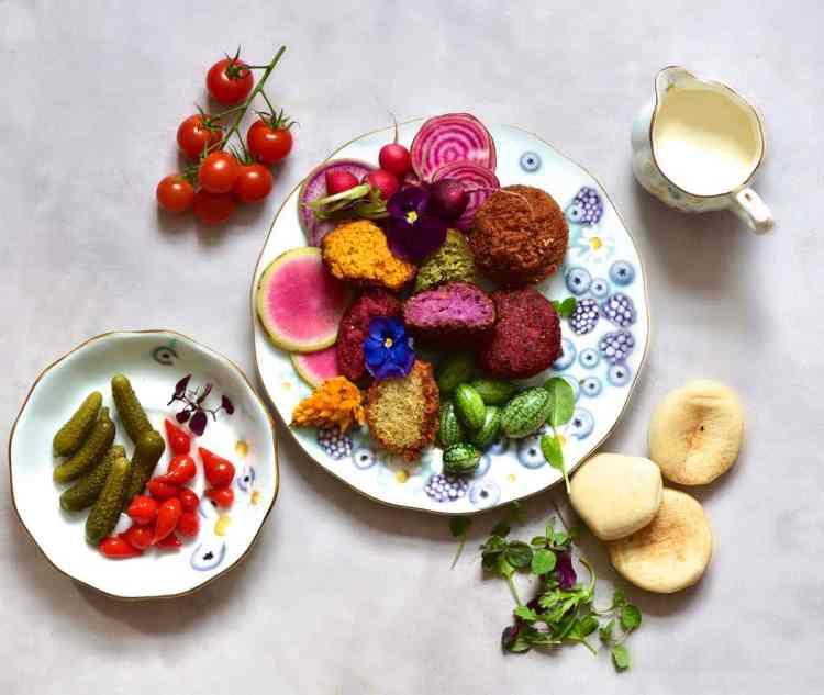 Rainbow falafel with veggies, yogurt vegan tahini dip, pita bread and edible flowers as part of a mezze platter