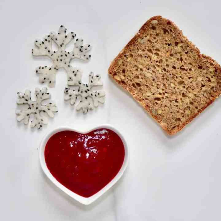 Ingredients for a Christmas healthy toast recipe with homemade cranberry sauce and dragonfruit snowflakes