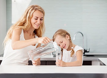 Child with Mother Drinking Water from Glass in Kitchen