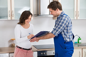 Happy Woman Writing on Clipboard in Front of Young Plumber Standing in Kitchen