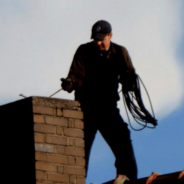 man sweeping chimney on roof