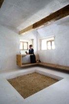 Peter Haimerl Architekt. Ins Innere des alten Bauernhauses goss der Architekt Peter Haimerl vier quadratische Betonkuben, um das Haus zu stützen und zu isolieren. Öffnungen im Beton geben den Blick auf die alte baufällige Fassade frei