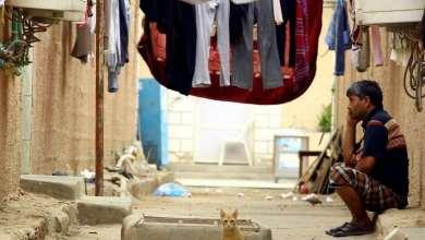 صورة تظهر عامل آسيوي يجلس في منزله في مخيم عمال القادسية بالسعودية/رويترز