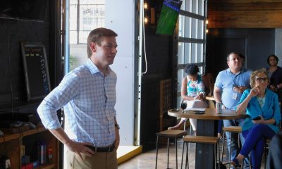 Eric Swalwell stands by a window before a crowd