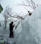 Man standing next to 10 foot snow bank