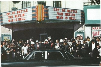 Lee Harvey Oswald being pushed into a police car in front of the Texas Theater