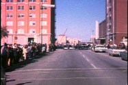 Frame from early segment of Hughes film showing car turning corner by Texas School Book Depository
