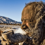 Amou Haji smokes animal feces from his pipe