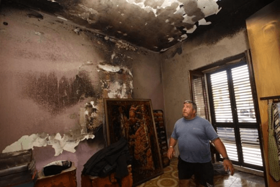 A Canneto di Caronia man examines damage from a mysterious fire