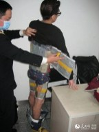 Police remove plastic and tape from man's back to reveal iPhones he was attempting to smuggle