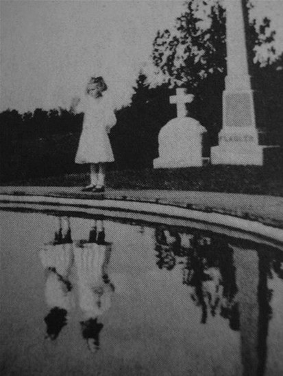 This photo was taken of a girl at a gravesite.  It was not until years later than the strange anomaly was noticed – early 1900's.