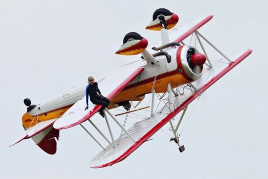 Wing walker Jane Wicker sitting on the wing of the airplane mere seconds before it crashes