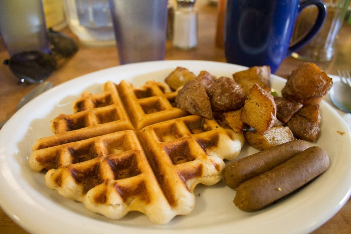 plate of vegan waffles with Field Roast maple sausage, and home fries at Paradox Cafe in Portland