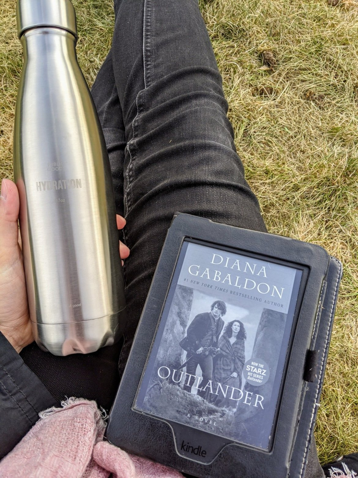 """Water bottle and Kindle with cover of """"outlander"""""""