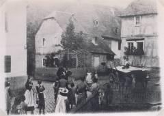 """""""Die alten Straßen noch, die alten Häuser noch"""" - Wahrscheinlich war es ein unterhaltsames Sonntagsvergnügen für die Kinder, als etwa 1895 ein kleiner Wanderzirkus mit einem Tanzbär die Dorfstraße in Waldbreitbach belebte und eine bescheidene Abwechslung in die örtliche Szene brachte. Deutlich ist die enge Straße mit der klobigen Pflasterung an der Ecke beim """"Gasthaus Becker"""" und dem noch bestehenden Backhaus zu erkennen. Direkt gegenüber das Haus der damaligen Metzgerei Wolf Jonas. Links das um 1780 erbaute Häuschen der Witwe Helene Schicker, das 1912 durch ein modernes Gebäude ersetzt wurde. (Richard Schicker 1995)"""