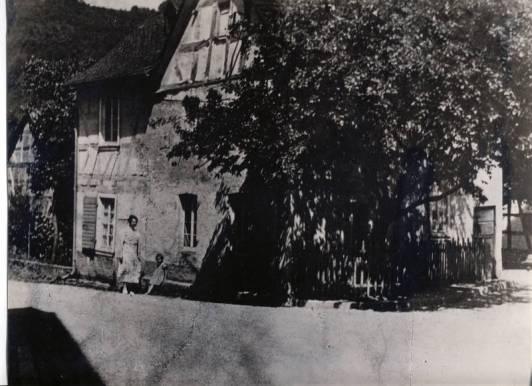 """Noch kann sich vor dem ehemaligen Haus """"Nassen"""" an der Brückenstraße Ecke Hauptstraße der morsche Quittenbaum gegen den Verkehr behaupten. Die alte Schmiede im Hintergrund wird von dem Wohnhaus verdeckt. Das Häuschen gehörte der Familie Nassen, die hier etwa bis zur Jahrhundertwende mit dem Schmiedehandwerk ihren Broterwerb sicherte. Manche wissen noch von der alten zweiteiligen Eingangstüre dieses Hauses zu berichten, die um 1936/40 in Waldbreitbach hier und dort noch vorhanden waren. Die letzten """"Nassen's"""", welche das Haus bewohnten, waren Caroline und Gretchen sowie Bruder Hermann Nassen, die nach ihrer Ausbildung aus beruflichen Gründen in das Elsaß und später nach Düsseldorf verzogen sind. Caroline war dort Lehrerin. In das Häuschen zogen Mieter ein, doch gelegentlich beanspruchten die Geschwister Nassen einige Räume als Feriendomizil. Die Veröffentlichung des Bildes gibt Anlaß, über ein im wahrsten Sinne des Wortes """"mißliches Ereignis"""" zu berichten, von dem vor über einhundert Jahren an dieser Ecke zwei Waldbreitbacher Schülerinnen unangenehm betroffen wurden. Gretchen, das Töchterlein eines örtlichen Schneidermeisters und die Müllerstochter Anna, beide 1884 in Waldbreitbach geboren, hatten den gleichen Weg zur zweiklassigen Schule. Standort der """"Alten Schule"""", die 1838 erbaut wurde, war das Terrain des heutigen Platzes """"am alten Kreuz"""". Nach dem Schulunterricht an dem fraglichen Tage um 1895 oder 1896 machten die beiden Mädchen sich auf den Heimweg. Just in dem Moment, als die Schülerinnen nichtsahnend an dem Haus """"Nassen"""" vorübergehen, öffnet sich das kleine Fenster im Giebel und irgendwer entleerte mit gebührendem Schwung den vermutlich gut gefüllten Nachttopf auf die Straßengosse aus. Den Nachttopf so zu leeren war zu dieser Zeit auch in Waldbreitbach keine Seltenheit. Der """"Zeipe Bach"""" besorgte vermutlich dann und wann die notwendige Spülung. In ihren adretten Kleidchen von dem fatalen Inhalt durchnäßt und nicht unerheblich bekleckert, blieb den """"Armen"""" ni"""