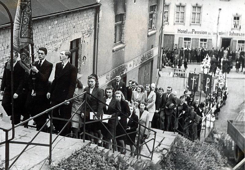 Erste Fronleichnamsprozession nach dem 2. Weltkrieg 1946 Noch deutliche Kriegsschäden sind an der Fassade des Hauses von Sattler und Polsterer Johann Schmitz an der Kirchtreppe zu sehen