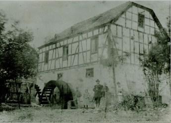 Foto der Mühle von 1905- Das linke Wasserrad treibt den Kollergang (Ölquetsche), das rechte die zwei Mahlgänge. Im Fenster über dem Rad Wilhelm, rechts sein Bruder Jakob Nassen. (Bildquelle: Heiner Strauß, St. Katharinen)