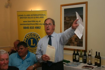 Len Mills as Auctioneer
