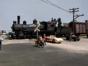 A pair of cyclists wait at the crossing as a freight train passes through Pine Bluffs