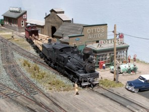 A lumber train passes Otto's Autos