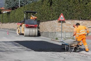 Operai a lavoro per asfaltare una strada