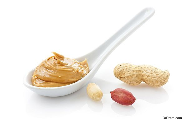 Creamy peanut butter in a white spoon with peanuts