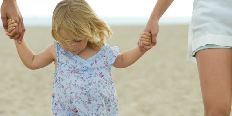 Little girl walking on beach while holding hands of parents.