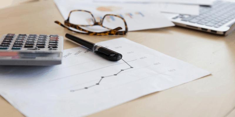 eyeglasses, pen and paper, symbolizing Retirement Planning
