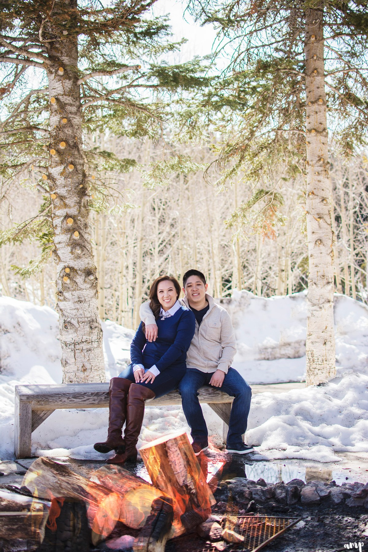 Engaged couple sitting beside bonfire surrounded by snow
