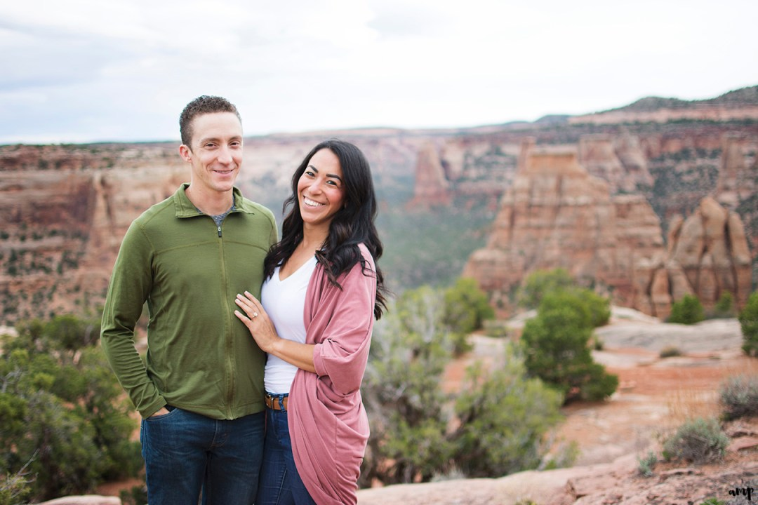 Engaged couple standing before a canyon in the Colorado National Monument