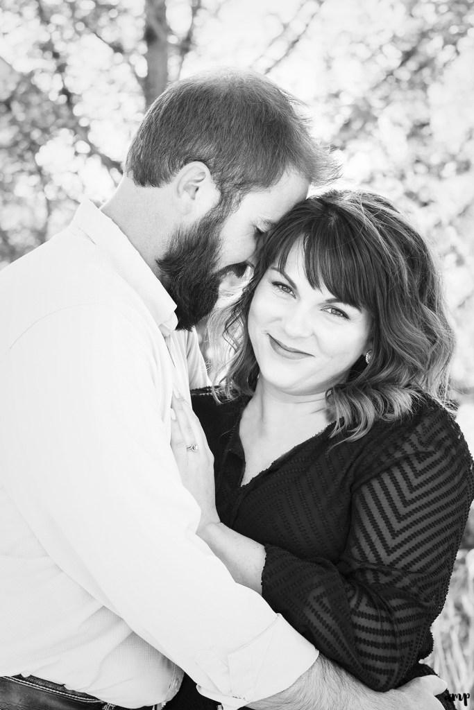 Black and white photo of engaged couple cuddling