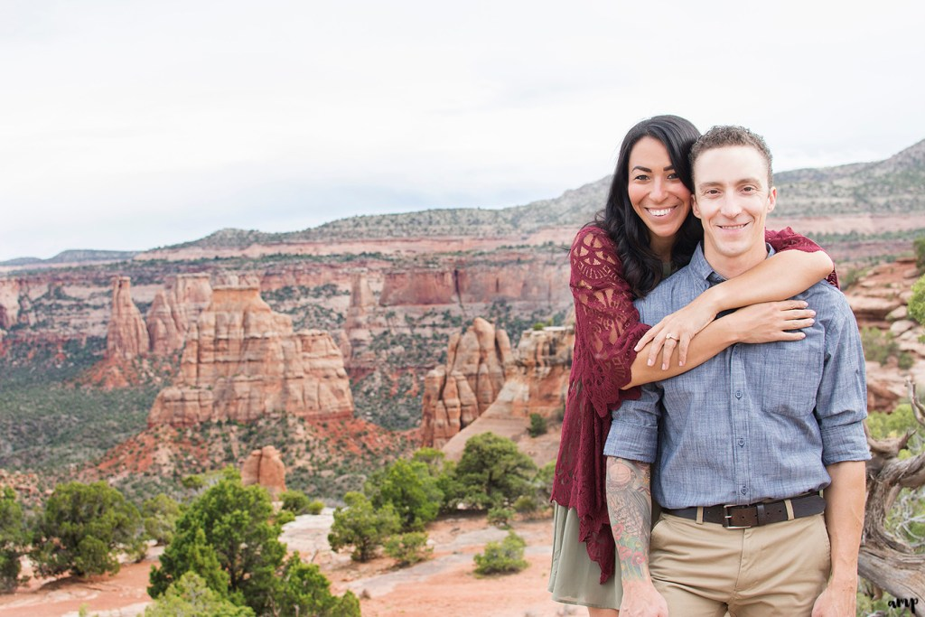 Couple standing near red rock formations in the desert