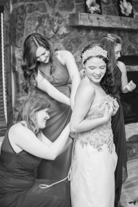 Bride with her bridesmaids lacing up her wedding dress