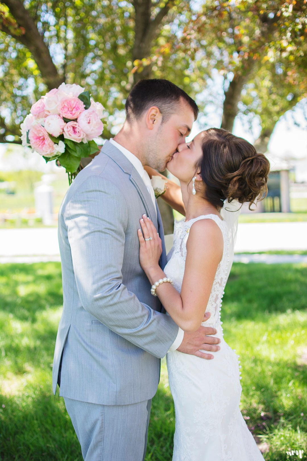 Bride and groom kissing in the shade of a tree