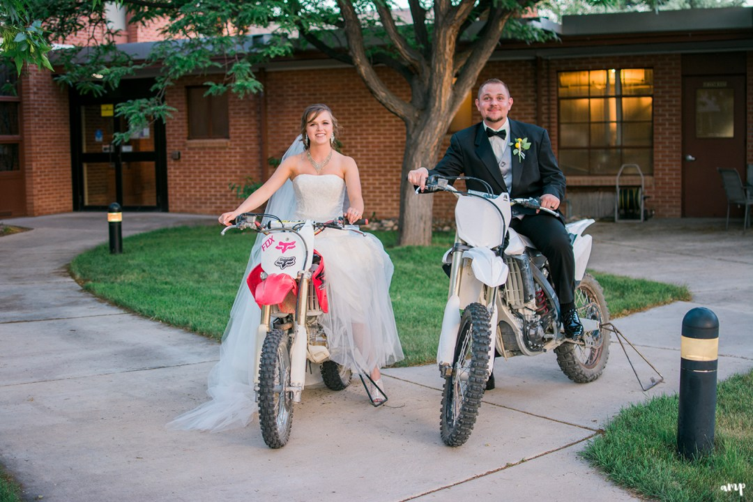 Bride and groom riding dirt bikes