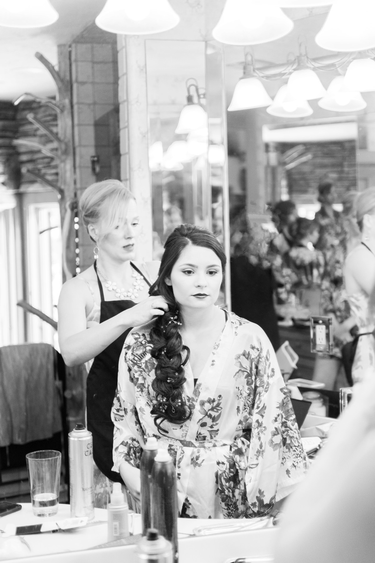 Bride looking into mirror while getting her hair done
